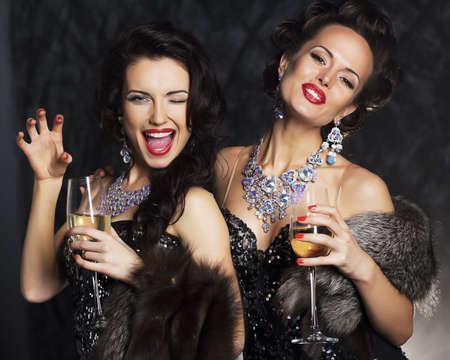 Jonge vrouwen in zwarte elegante jurk houden bekers met wijn - het nachtleven Stockfoto