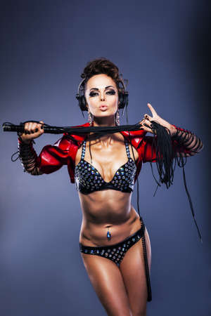 Sexy fetish woman dj  in lingerie holding whip with headphones listening to the music photo