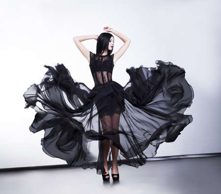 sensuality: Fantasy.  Fashionable sexy woman in fluttering black modern dress Stock Photo