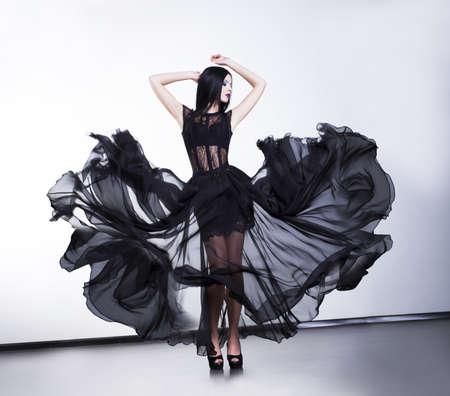 Fantasy. Fashionable woman in fluttering black modern dress