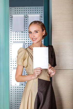 Smiling business woman holding a white blank paper - banner with copy space for text Stock Photo - 16441263