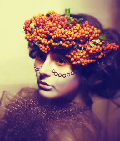 Fairy tale. Floristics. Woman in wreath of rowan berry - grunge photo