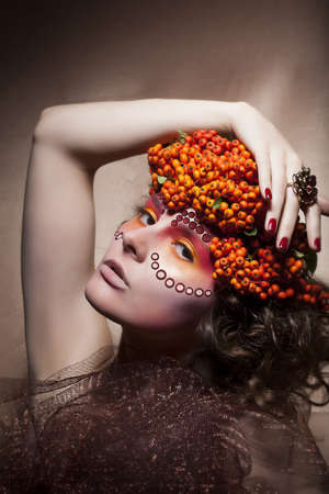 Rowan berry - autumn sorb wreath. Retro style. Beauty woman face photo