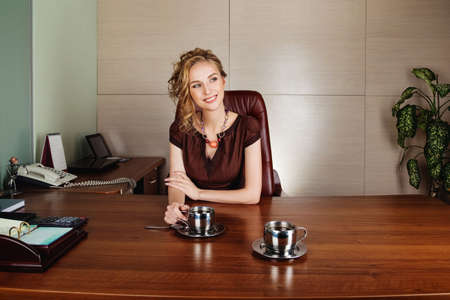 Cute happy businesswoman working at the office and smiling Stock Photo - 16536682