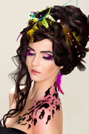 Womans beauty face with bright makeup and feathers - ornate photo