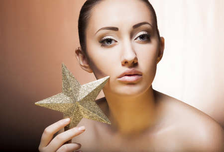 Woman with golden star. Professional soft make up photo