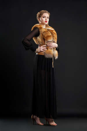 Fashion woman in Fur Collar and modern Dress Posing in Studio photo