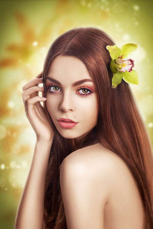 Beautiful brunette Model with Healthy Straight Hair with Flower photo