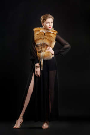 Fashionable Woman in Luxury Fur Coat  over Black Background photo