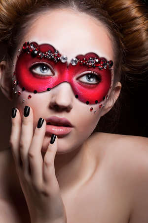 Painted Face  Beauty Woamn in Red Carnival Mask  Masquerade photo
