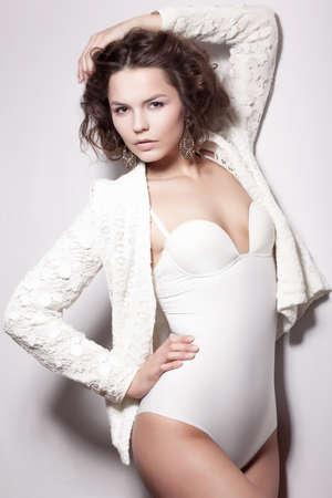Alluring Shiny Supermodel Female posing in White Retro Underwear Stock Photo - 17130046