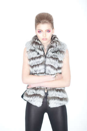 Stylish Trendy Young Woman in Fur Waistcoat and Leggings Posing in Studio photo