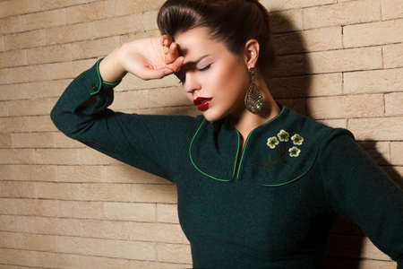 offense: Aristocratic Brown Hair Sad Woman in Green Dress over Brick Wall