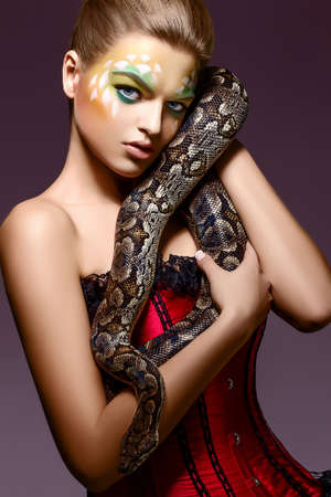 Beautiful Woman holding Python Snake in Hands - Performance photo