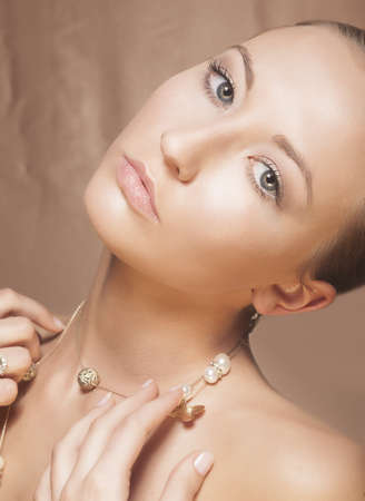 Beauty Woman Face. Elegant Golden Necklace with Pearls photo