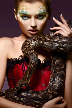 Serpent. Fantasy. Fancy Woman holding Tamed Snake in Hands photo
