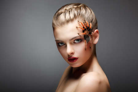 Portrait of Spider-Girl Fashion Model with Poisonous Spider on her Face photo
