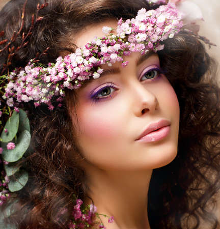 Closeup Portrait of Pretty Woman with Wreath of Pink Flowers. Natural Beauty photo