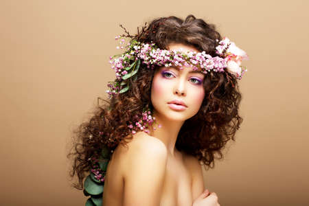 8 March. Springtime. Beauty Woman with Wreath of Flowers over beige photo