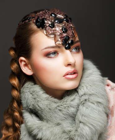 trenzas en el cabello: La mujer del pelo trenzado de lujo en cuello de piel y piedras preciosas. Joyas Foto de archivo