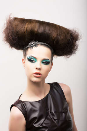 Peculiar Emotional Girl with Odd Creative Styling. Fantastic Hairdo. High Fashion photo