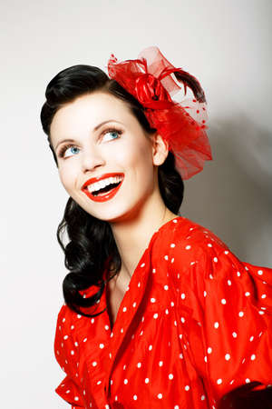 Retro Style. Elation. Portrait of Happy Toothy Smiling Woman in Pin Up Red Dress photo
