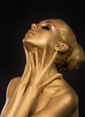 coberto: Coloração. Gilt. Rosto de ouro da mulher Chapada. Conceito de arte. Corpo dourado. Concentre-se em suas mãos