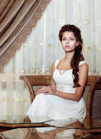 nifty: Femininity. Brown Hair Woman Bride in Wedding Dress sitting. Classic Romantic Interior Stock Photo