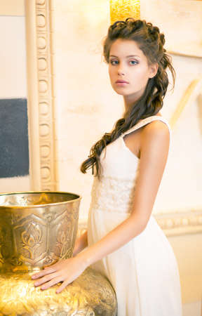 Luxurious Posh Brunette in White Dress. Oriental Antique Golden Decor Stock Photo - 18462470