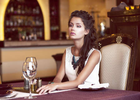 Dating. Dreaming Woman waiting at Decorated Table in Restaurant Interior photo