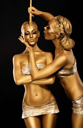 maquillaje de fantasia: Fantasía. Creatividad. Mujeres brillantes los Cuerpos dorados de oro. Letras Foto de archivo