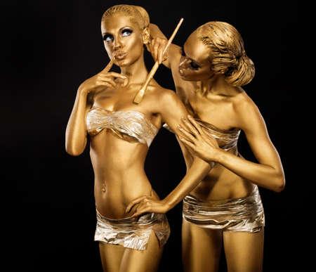body paint: Body Art. Mujer pintura corporal con pincel en color dorado. Oro Make Up