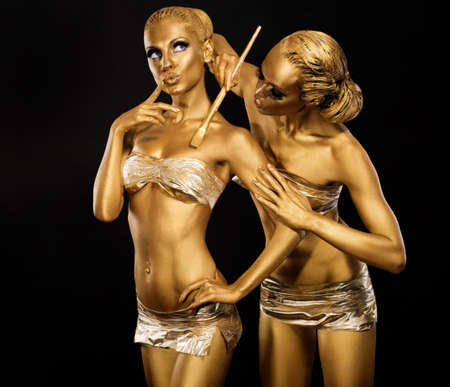 brush in: Body Art. Woman painting Body with Paint Brush in Golden Color. Gold Make Up Stock Photo