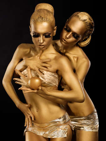 Glitter. Glaze. Seductive Women with Golden Bodies Hugging. Fantasy photo