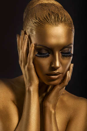 Face Art. Fantastic Gold Make Up. Stylized Colored Womans Body photo