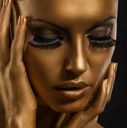 haute couture: Gilt. Golden Womans Face Closeup. Futuristic Giled Make-up. Painted Skin