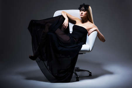 Enjoyment. Classy Elegant Woman Blonde relaxing in Chair. Black Dress and Mask with Feathers photo