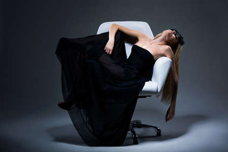 Harmony & Sensuality. Romantic Blond Female in Black Dress resting in Armchair. Satisfaction Stock Photo - 18462516
