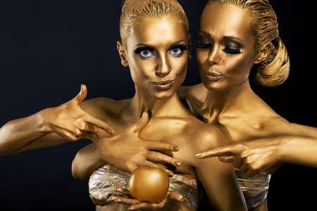 Masquerade. Enjoyment. Two Glossy Women with Golden Body Art. Glamor Stock Photo - 18462517