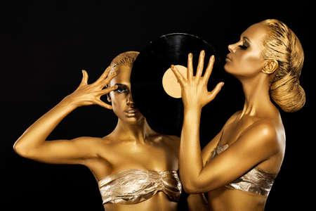 record: Fetish. Women DJs holding Retro Vinyl Record. Fantastic Gold Badyart. Performance Stock Photo