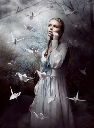 woman flying: Night. Woman in  Mysterious Forest launching handmade paper Cranes. Origami Stock Photo