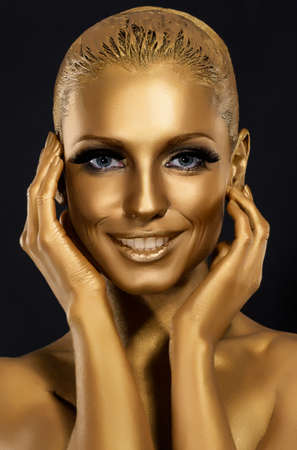 painted face: Coloring & Glance. Gorgeous Woman smiling. Fantastic Golden Makeup. Art
