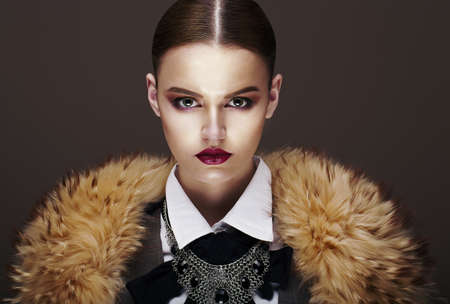 strict: Beautiful Fashionable Strict Fashion Model in Fur Coat. Luxury