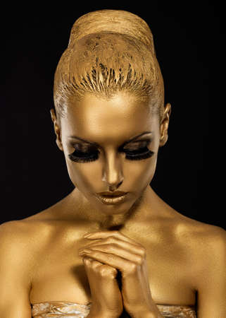 kneeling woman: Belief. Styled Woman with praying hands. Golden Makeup