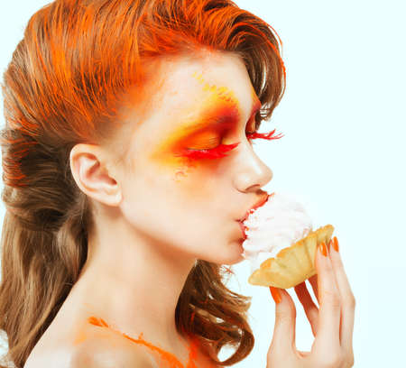 Coloring. Creativity. Profile of Red-haired Woman eating a Cake with Cream. Blush photo