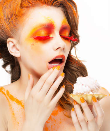 tempting: Gilding. Tempting Woman eating a Pie with Cream. Bright Red-Golden Makeup