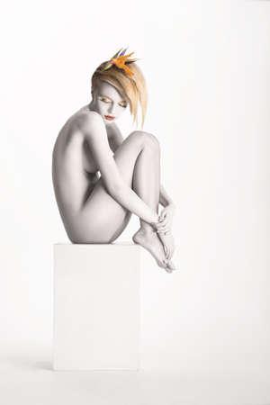 Fantasy. Harmony. Beauty Muse sitting over White Background. Bodyart - Platinum Painted Skin Stock Photo