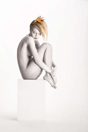 naked young girl: Fantasy. Harmony. Beauty Muse sitting over White Background. Bodyart - Platinum Painted Skin Stock Photo