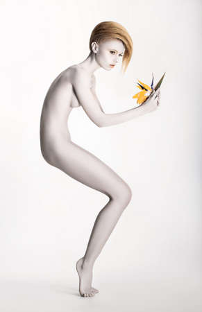Imaginary. Expressive Undressed Woman in Fantastic Graceful Pose. Statue with Flower