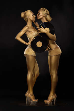 Futurism  Creativity  Glossy Gloden Women with Vinyl Record over Black  Shiny Gilded Bodyart photo